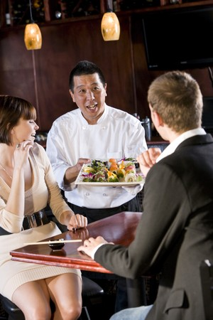 Japanese sushi chef serving platter of sushi to young couple photo