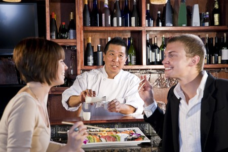 Sushi chef serving young couple in Japanese restaurant 스톡 콘텐츠