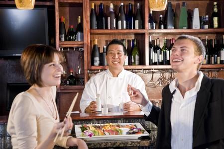 일본 레스토랑에서 젊은 부부를 제공하는 스시 요리사