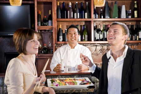 Sushi chef serving young couple in Japanese restaurant Stok Fotoğraf