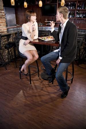 pareja comiendo: Pareja comer sushi en restaurante japon�s de conversaci�n  Foto de archivo