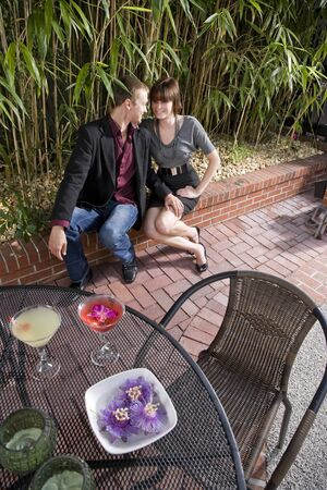 Young romantic couple having cocktails on patio photo