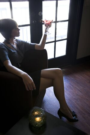 Silhouette of young woman sitting alone in dark room drinking photo