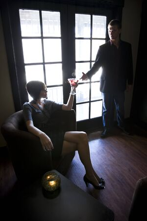 Young couple in dark room, woman holding drink photo
