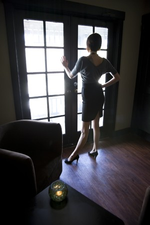 Silhouette of young woman looking out window in dark room