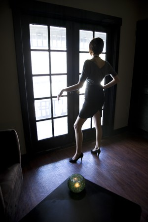 Silhouette of young woman looking out window in dark room photo