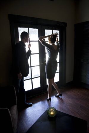 Silhouette of young couple standing by window in dark room talking photo