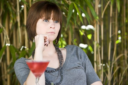 Young sexy contemplative woman outdoors with cocktail photo