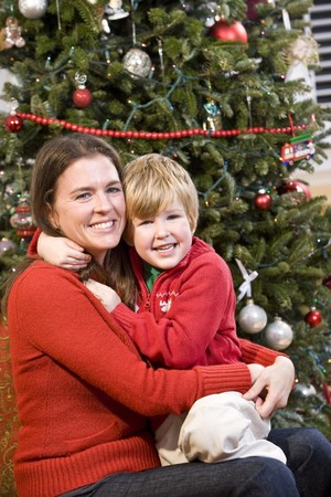 Mother and 4 year old boy hugging in front of Christmas tree Stock Photo - 7635160