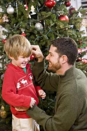 Father and 4 year old son playing in front of Christmas tree Stock Photo - 7635143