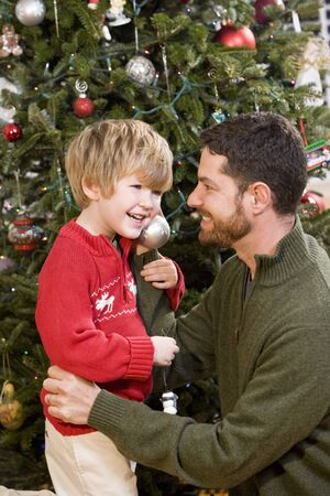 Father and 4 year old son playing in front of Christmas tree Stock Photo - 7635139