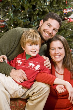 Family with 4 year old boy sitting in front of Christmas tree Stock Photo - 7635153