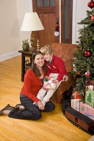 Mother with 4 year old boy holding present by Christmas tree Stock Photo - 7635130