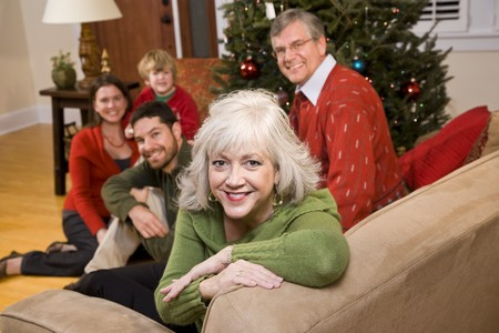 Senior woman with family by Christmas tree - three generations photo