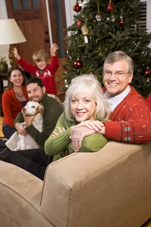 seniors homes: Senior couple with family by Christmas tree - three generations Stock Photo