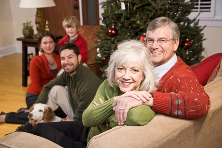 Senior couple with family by Christmas tree - three generations photo
