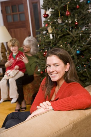 three generations of women: Three generations - happy mother at Christmas with boy and grandmother in background