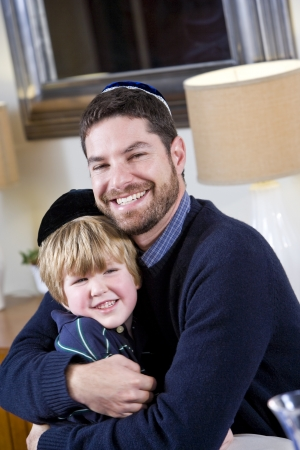 Loving Jewish father and young 4 year old son wearing yarmulkes photo