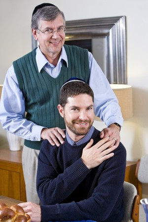 Portrait of senior Jewish man with adult son wearing yarmulkes photo