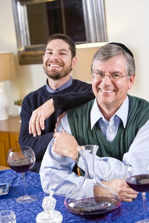 Senior Jewish man and adult son celebrating Hanukkah photo