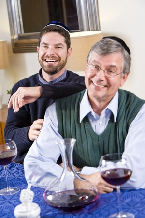 yamaka: Senior Jewish man and adult son celebrating Hanukkah