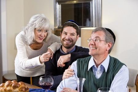 jewish home: Mid-adult Jewish man at home smiling with senior parents
