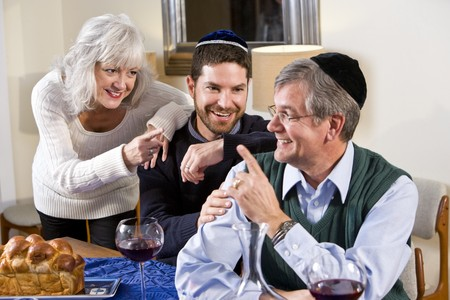 Mid-adult Jewish man at home smiling with senior parents photo