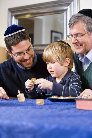 jewish people: Boy with father and grandfather spinning dreidel, celebrating Hanukkah