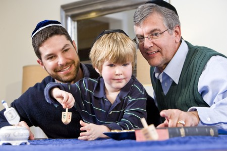Boy with father and grandfather spinning dreidel, celebrating Hanukkah