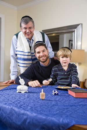 Boy with father and grandfather spinning dreidel, celebrating Hanukkah Stock Photo - 7634902
