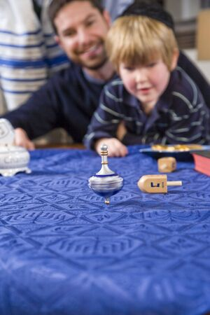 Boy with father and grandfather spinning dreidel, focus on dreidel photo