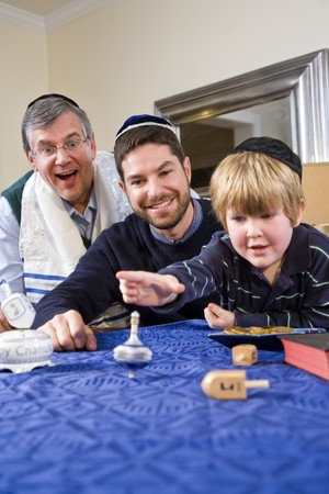 Boy with father and grandfather spinning dreidel, celebrating Hanukkah photo