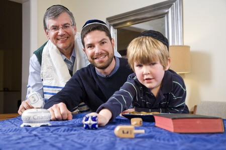 yamaka: Boy with father and grandfather spinning dreidel, celebrating Hanukkah