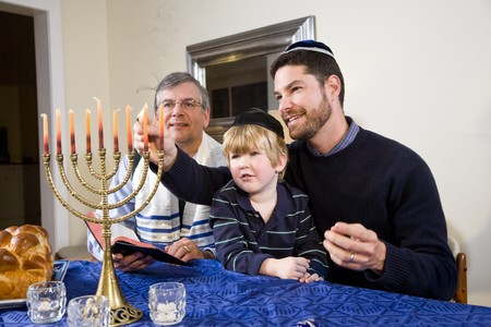 Three generation Jewish family lighting Chanukah menorah photo