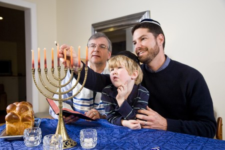 judaism: Three generation Jewish family lighting Chanukah menorah
