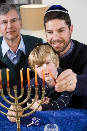 Three generation Jewish family lighting Chanukah menorah Stock Photo - 7635080