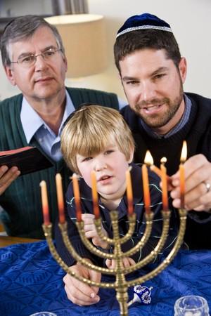 Three generation Jewish family lighting Chanukah menorah photo
