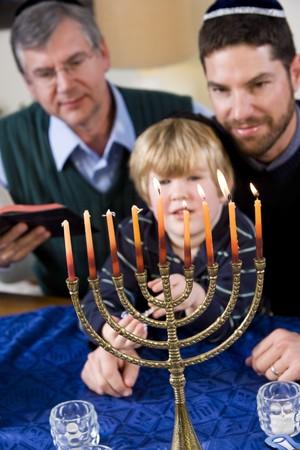 Three generation Jewish family lighting Chanukah menorah