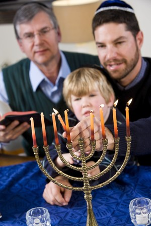 yamaka: Three generation Jewish family lighting Chanukah menorah