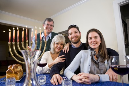 Jewish family celebrating Chanukah at table with menorah Stok Fotoğraf