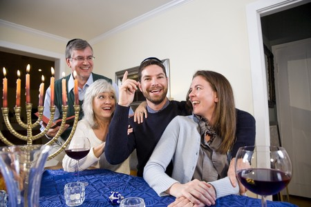 Jewish family celebrating Chanukah at table with menorah Stok Fotoğraf