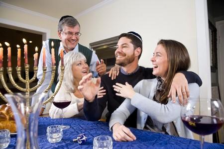 Jewish family celebrating Chanukah at table with menorah Stock Photo - 7635060