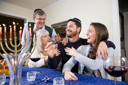 Joodse familie vieren Chanukah aan tafel met menora