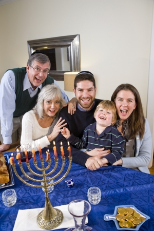 Jewish family celebrating Chanukah at table with menorah Stok Fotoğraf - 7635104