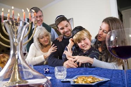 three generations: Jewish family celebrating Chanukah at table with menorah Stock Photo