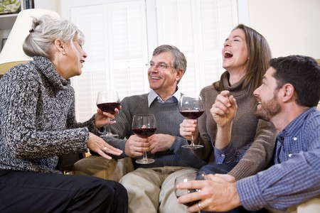 red sofa: Senior couple with adult children conversing and drinking wine