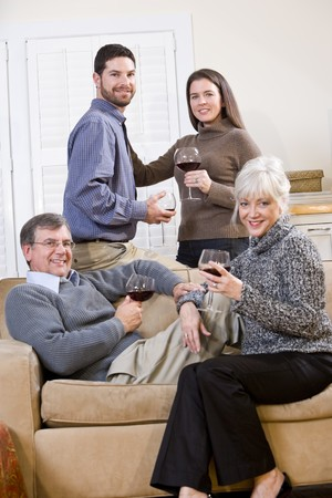 Senior couple with adult children conversing and drinking wine photo