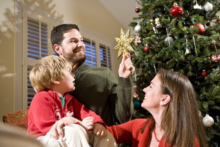 Family with child by Christmas tree, dad holding star photo
