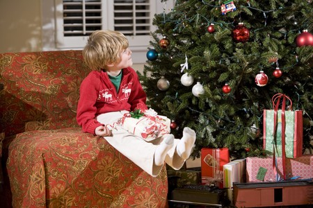 Little boy looking up at Christmas tree with present in lap photo
