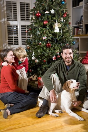 Family with 4 year old boy and dog by Christmas tree photo